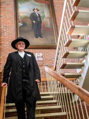Eric Burkhardt, educator, thespian and Information Services specialist, stands before an artistic rendering of Robert Morrison. Burkhardt has many times portrayed the founder of Morrisson-Reeves Library, whose gift to the community still positively affects East Central Indiana.