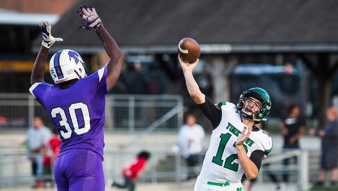 Central's Kenny Coleman, left, tries to block a pass from Yorktown's Reid Neal during their game at Central Friday, Aug. 25, 2017.