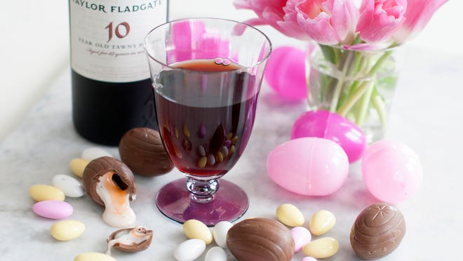 A glass of Taylor Fladgate 10-year-old Tawny Porto surrounded by milk chocolate Cadbury creme eggs Easter candy.