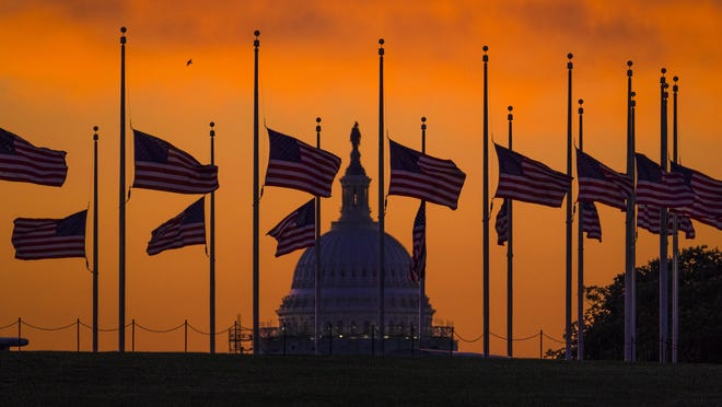 OUT OF CAMERA FILE - Flags fly at half-staff around the Washington Monument at daybreak in Washington with the US Capitol in the background Monday, June 13, 2016. President Barack Obama ordered flags lowered to half-staff to honor the victims of the Orlando nightclub shootings. (AP Photo/J. David Ake.)