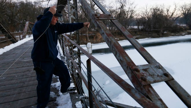 Bill Blubaugh, a lab technician with Des Moines Water Works, lowers a collection bottle off the Bill Riley Trail bridge in January as he takes water samples at multiple points along the Raccoon River in Des Moines.