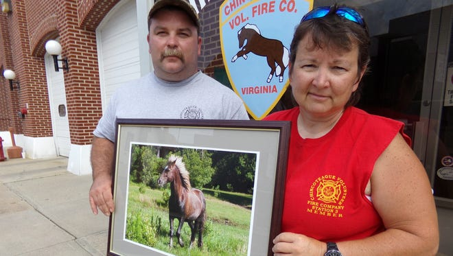 Lottery for life winner Denise Bowden of Chincoteague is pictured with Booby Lapin of the Chincoteague Volunteer Fire Company holding  a framed photograph of the island's famed pony, Surfer Dude.