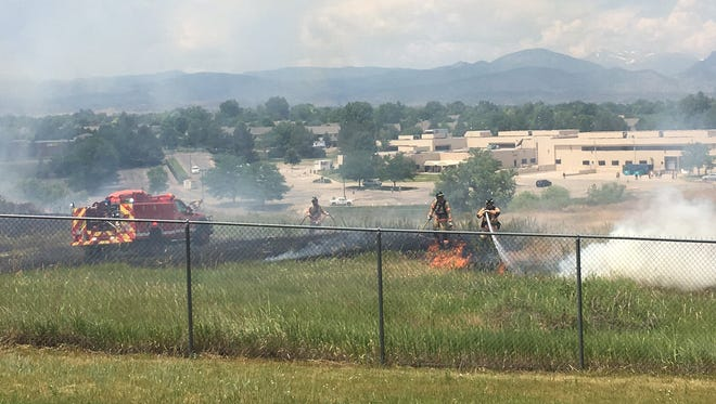Firefighters from across Northern Colorado worked to contain a nearly 6-acre grass fire Wednesday afternoon in Loveland.
