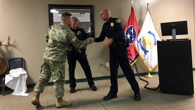 Capt. John Kile from Fort Campbell presents CPD's District 1 Capt. David Crockarell and Traffic Unit Sgt. Johnny Ransdell with commemorative coins.