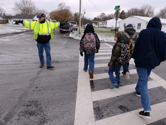 Bob Jumper stops traffic on Talmadge Avenue as students