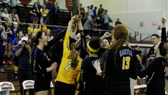 Castle celebrates Saturday after winning the 2015 IHSAA volleyball sectional against North at Harrison High School.
