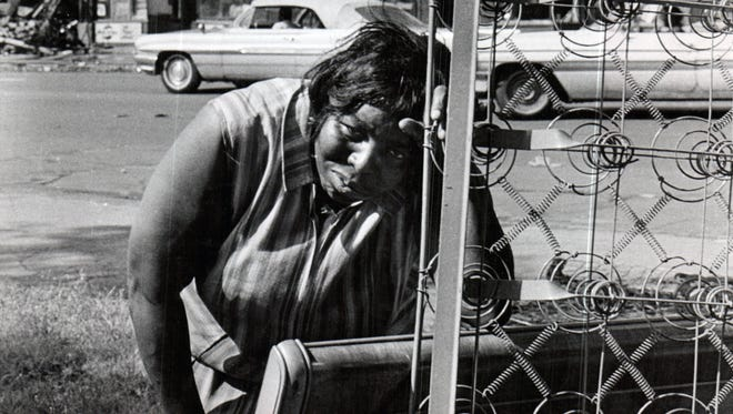 A Detroit woman rests on a mattress in the early morning hours of Sunday, July 23, 1967.