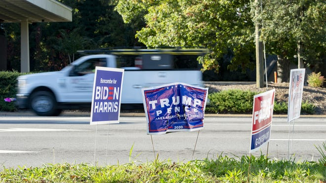 Political signs are posted on a small grassy median on Patton Avenue and Haywood Road in West Asheville on Oct. 12, 2020.