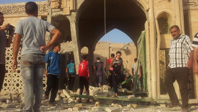 People inspect the destroyed Mosque of The Prophet Younis, or Jonah, in Mosul, 225 miles  northwest of Baghdad, Iraq, July 24, 2014. The revered Muslim shrine was destroyed on Thursday by militants who overran the city in June and imposed their harsh interpretation of Islamic law.