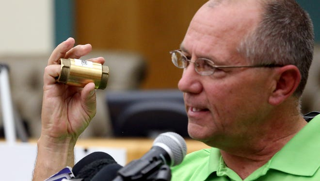 Mayor Dan McQueen displays a backflow preventer as he talks to the media during a news conference Saturday, Dec. 17, 2016, at City Hall in Corpus Christi.