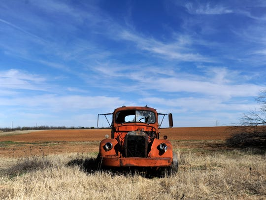 An old pickup slowly disintegrates in a field off State