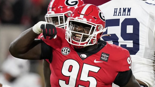 Georgia defensive lineman Jordan Davis (99) celebrates after sacking Auburn quarterback Bo Nix during the first half on Saturday night in Athens. Georgia moved from No. 4 to No. 3 in The Associated Press poll.