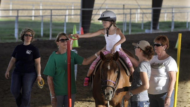 Teresa Douglass/visalia times-deltaInstructor Klara Bergtholdt, left, volunteers Shirley Van Wormer, Caitlyn Wainwright and Lyn Awbrey, right, look on as Brooke Jordan, 8, of Lemoore, reaches to place a red ring around a red pole at Happy Trails Riding Academy Sept. 9. Instructor Klara Bergtholdt, left, volunteers Shirley Van Wormer, Caitlyn Wainwright and Lyn Awbrey, right, look on as Brooke Jordan, 8, of Lemoore, reaches to place a red ring around a red pole at Happy Trails Riding Academy Sept. 9.
