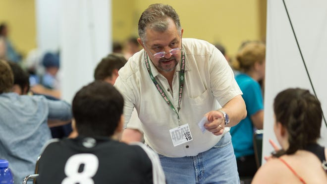 """Mike Sellers, an Indiana University-Bloomington professor and expert in game design, demonstrates his board game, """"Our Town,"""" with players at Gen Con at the Indiana Convention Center on Friday, July 31, 2015."""