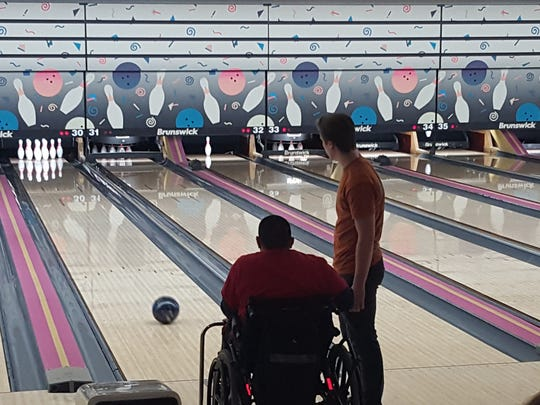 A Special Olympian watches as his bowling ball travels