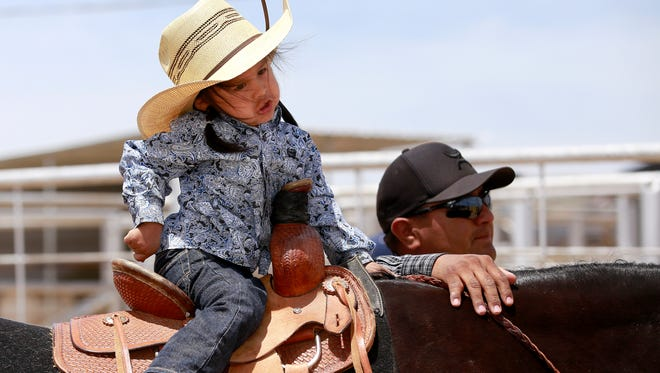 Jai Gunner Wilson, 2, of Shiprock, fidgets a little while waiting with his dad, Morgan Wilson, before the two did a walk-through of the pole bending course during the New Mexico Southwest Junior Rodeo Association May rodeo on Saturday at the San Juan County Sheriff's Posse rodeo grounds in Farmington.