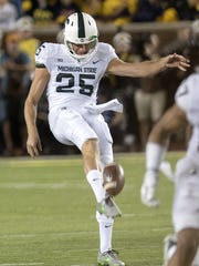 Michigan State's Jake Hartbarger punts against Michigan