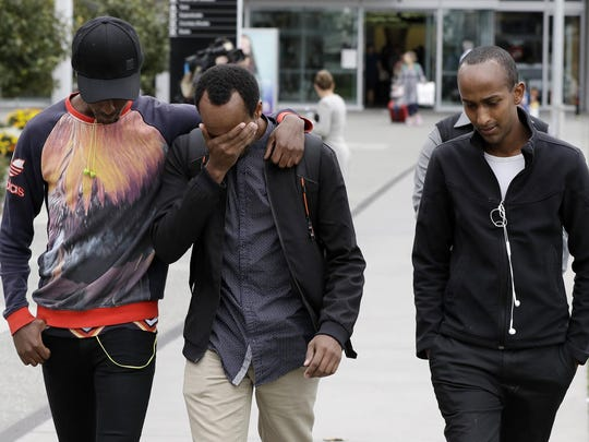 Abdifatah Ibrahim, center, and his brother Abdi, right, walk with an unidentified friend in Christchurch, New Zealand, Sunday, March 17, 2019. Abdifatah and Abdi are the older brothers of three-year-old Mucaad, who is the youngest known victim of the mass shooting in Christchurch, New Zealand on Friday, March 15.