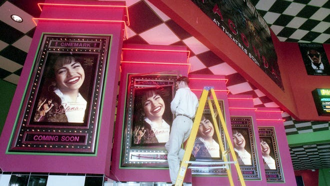 """Ely Marsh/Caller-Times fileA Tinseltown theater worker hangs up the movie posters for the """"Selena"""" movie premiere on March 13, 1997."""