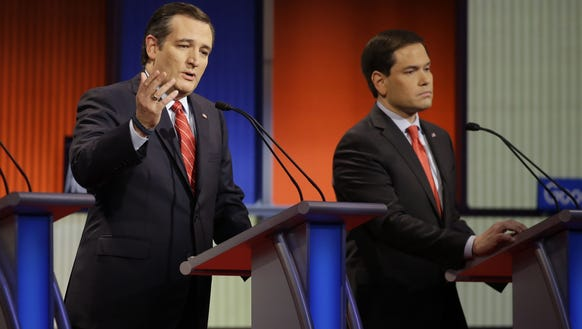 Ted Cruz speaks as Marco Rubio listens during the Republican