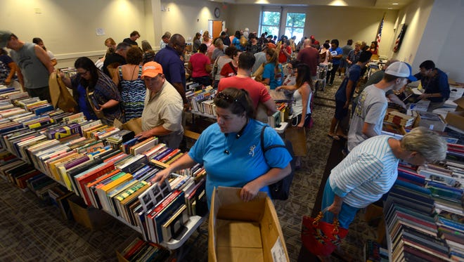 Shoppers scour the tables for reading material Saturday morning during the Five Dollar Blowout Book Sale at the main branch of the West Florida Public Library in Downtown Pensacola. For five dollars, shoppers were able to fill a bag with as many books as they wanted.
