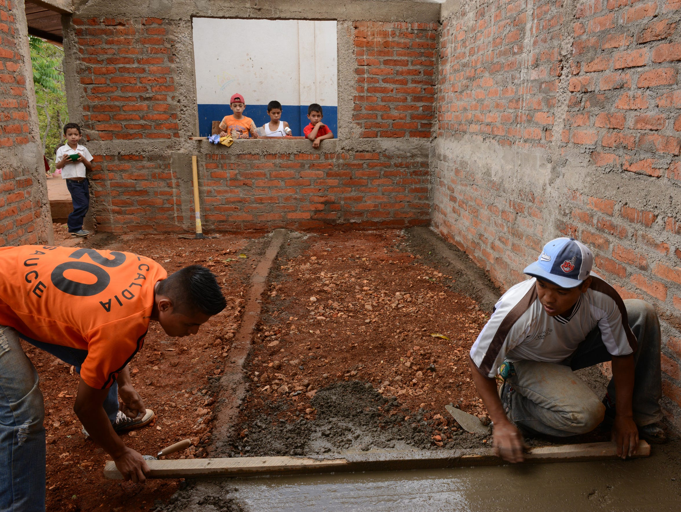 Using handmade bricks and simple tools, the team works