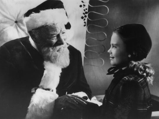 "Edmund Gwenn as Kris Kringle and Natalie Wood as Susan Walker in the 1947 film ""Miracle on 34th Street."""