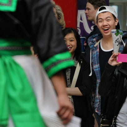 Joshua Xiong of Wausau reacts to two models in Hmong traditional clothing Sunday as Wausau Center mall hosted a fashion show and cultural showcase as part of the 10th annual Hmong Heritage Month celebration. Photos by Dan Young/Daily Herald Media