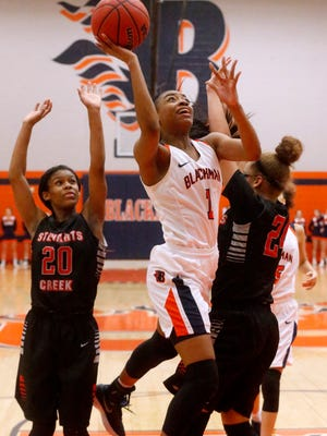 Blackman's Jaleah Goff (1) goes up for a shot between Stewarts Creek's Lauren Flowers (20) and Kaylee Odom Tuesday.