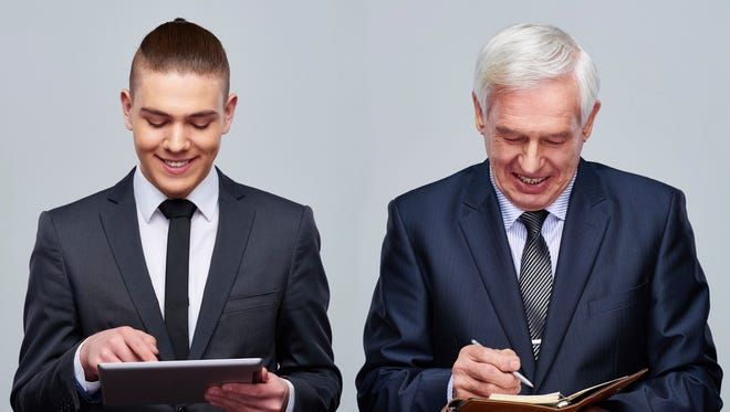Young businessman using digital tablet and senior businessman taking notes in personal organizer.