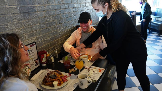 Reileigh Clark of Durham serves Hilary Kelsey of South Berwick, Maine, and Jonathan Goulis, a Massachusetts resident, inside the Roundabout Diner and Lounge in Portsmouth.