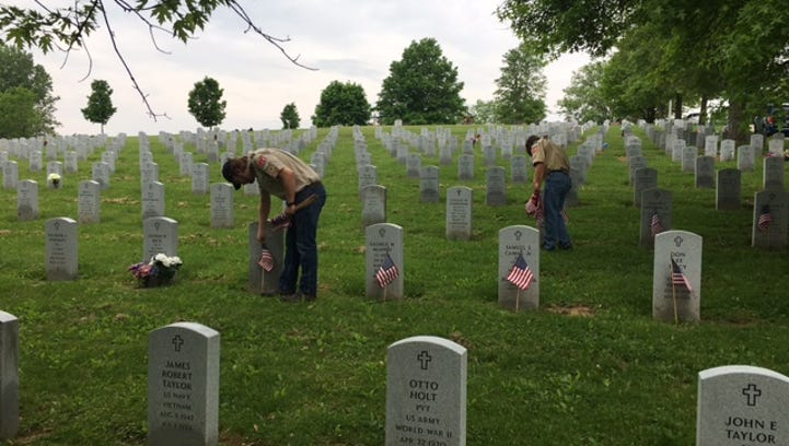Volunteers place flags at veterans' graves