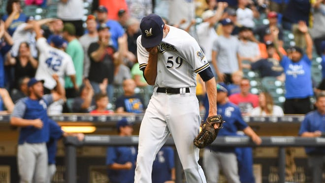 Milwaukee Brewers pitcher Carlos Torres gives up a grand slam in the ninth inning on Saturday.