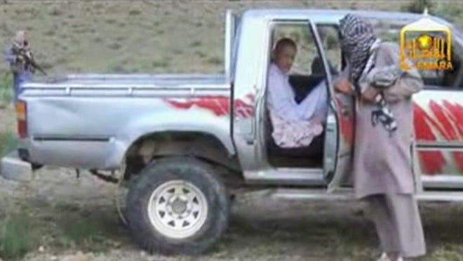 In this image taken from video obtained from Voice of Jihad website, which has been authenticated based on its contents and other AP reporting, Sgt. Bowe Bergdahl sits in a vehicle guarded by the Taliban in eastern Afghanistan.