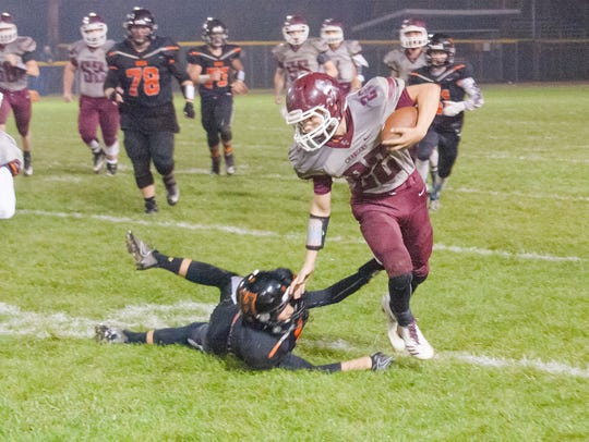 Union City senior Austin Mosher (22) breaks a tackle