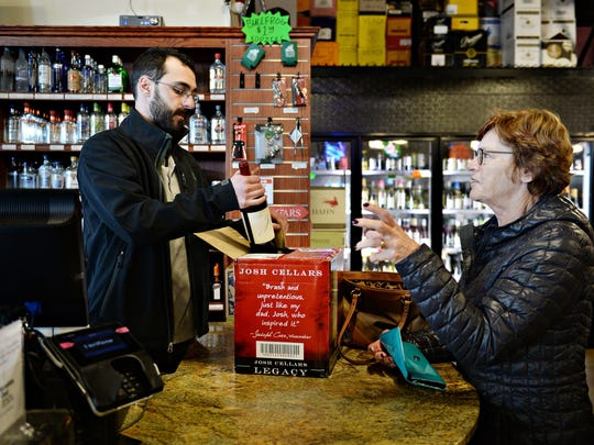 Jon Arena rings up a purchase for Kirsten Hovorka at Bullfrog Wine & Spirits Thursday at North College Marketplace. The store is expanding and adding a drive-thru window.