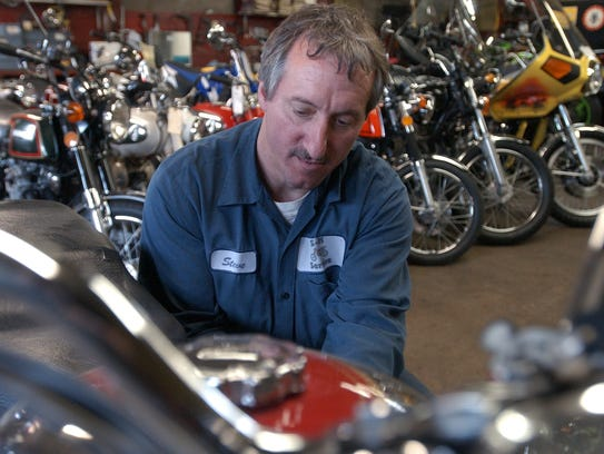 Steve Kasten tinkers with a Royal Enfield motorcycle