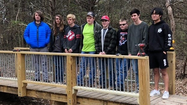 Volunteers stand on the Clysta Willett walking bridge after repairing it this past weekend.
