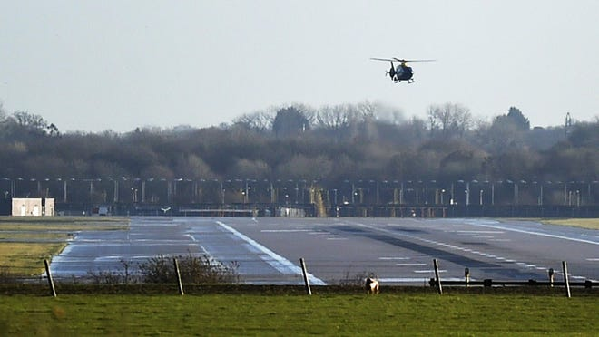 A police helicopter flies over the runway at Gatwick airport, London, as the airport remains closed with incoming flights delayed or diverted to other airports, after drones were spotted over the airfield last night and this morning, Dec. 20, 2018.
