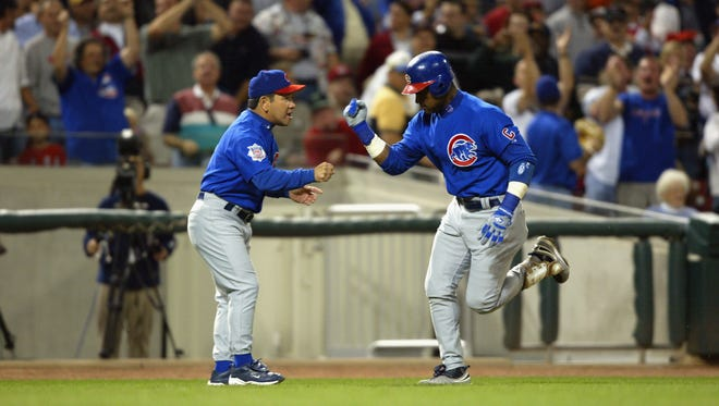 Sammy Sosa of the Chicago Cubs and third-base coach Wendell Kim celebrate Sosa's two-run home run against the Cincinnati Reds on September 25, 2003 at Great American Ball Park in Cincinnati, Ohio.