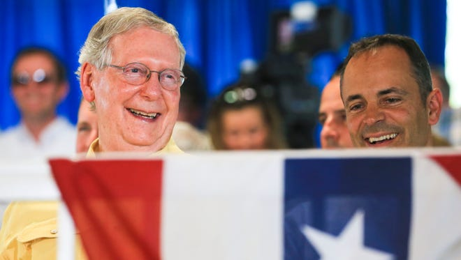 Senate Majority Leader Mitch McConnell and Kentucky Governor Matt Bevin laugh while listening to master of ceremonies Scott Jennings lambast politicians at the start of the speeches at the Fancy Farm picnic Saturday.