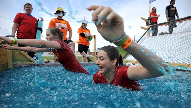 Karissa Grossman and Taren Mitchell spend as little time as possible in the Arctic Enema 2.0 obstacle during Tough Mudder on Saturday.