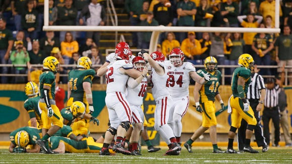 South Dakota kicker Miles Bergner is mobbed by his teammates after hitting a 33-yard field goal to beat NDSU 24-21 Saturday, Oct.17, 2015, at Gate City Bank Field at the Fargodome. David Samson / The Forum