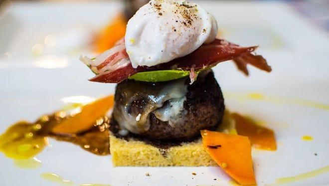 "The ""Royale with Cheese"" is a house-ground steak burger with Prairie Breeze cheddar, garlic shallot jam, avocado, country ham and a poached egg, served open face on sweet potato-onion brioche. Pictured is a smaller version of the burger served at a recent 10-course prix fixe Saturday Supper at Proof."