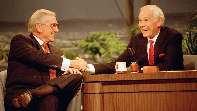 """Talk show host Johnny Carson (right) shakes hands with the show's announcer, Ed McMahon, during the final taping of """"The Tonight Show Starring Johnny Carson"""" on May 22, 1992."""