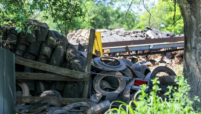 Tires are stacked behind a rope and a private property sign outside the office of Viva Recycling of South Carolina on Abbeville Road near Homeland Park.