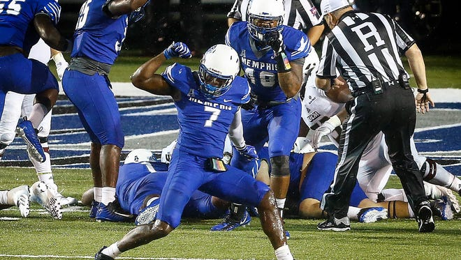 University of Memphis linebacker Curtis Akins (middle) celebrates after hitting University of Louisiana-Monroe running back Derrick Gore  (left) causing a fumble during second quarter action at the Liberty Bowl Memorial Stadium.