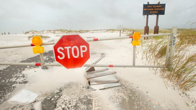 The road at the Gulf Islands National Seashore is covered with sand and debris after Hurricane Nate in Pensacola on Sunday, October 8, 2017.
