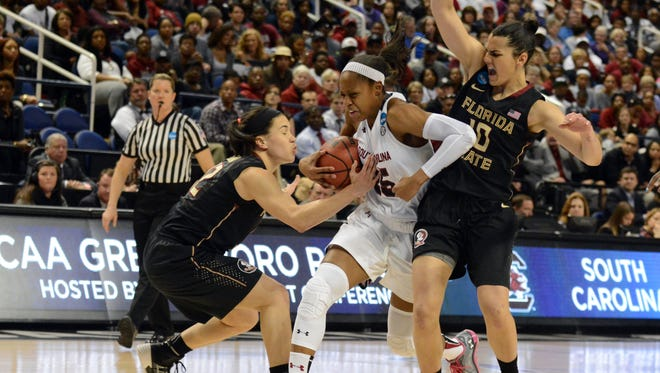 South Carolina Gamecocks guard Tiffany Mitchell (25) drives to the baskets as Florida State Seminoles guard Leticia Romero (10) and  guard Brittany Brown (12) defend during the first half in the finals of the Greensboro Regional of the 2015 women's NCAA Tournament at Greenboro Coliseum Complex