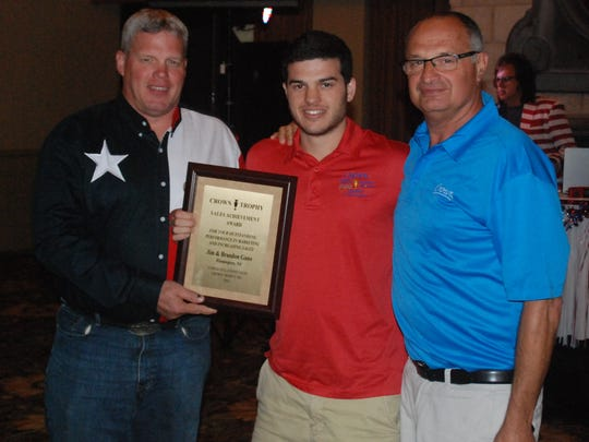 Crown Trophy of Flemington received four awards at this year's annual franchisee meeting in Austin, Texas. Owner Jim Gano, left, and his son, Brandon, right, are pictured with Crown Trophy founder Chuck Weisenfeld.